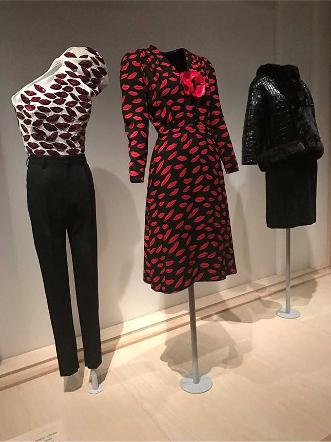 Left: Ensemble by Hedi Slimane (French, born 1968) for Yves Saint Laurent (French, founded 1966), Spring/Summer 2014. Blouse made from white silk crepe, embroidered with lip motifs in white iridescent and red plastic sequins and black glass beads; trousers made from black wool gabardine. Gift of Maison Yves Saint Laurent, 2015. Centre: Dress (1971) by Yves Saint Laurent (French, 1936-2008) in black and red printed rayon crepe with red vinyl flower. Purchase, Gould Family Foundation Gift, 2010