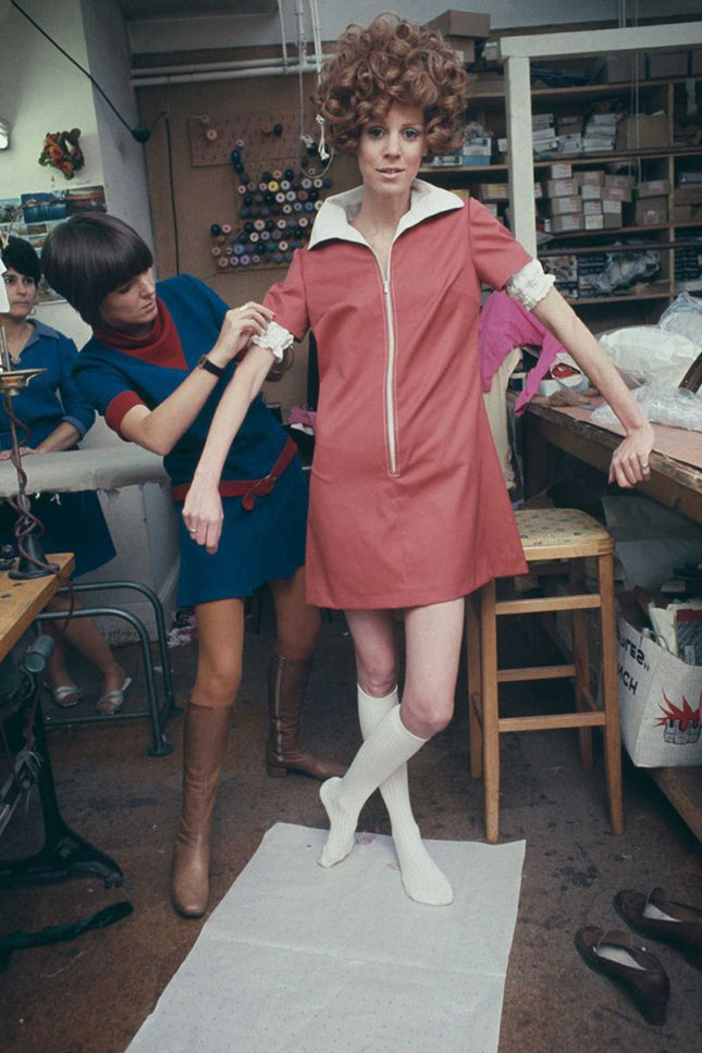 British fashion designer Mary Quant making final adjustments to a zip-up mini-dress on a fashion model in her London design studio, January 1967