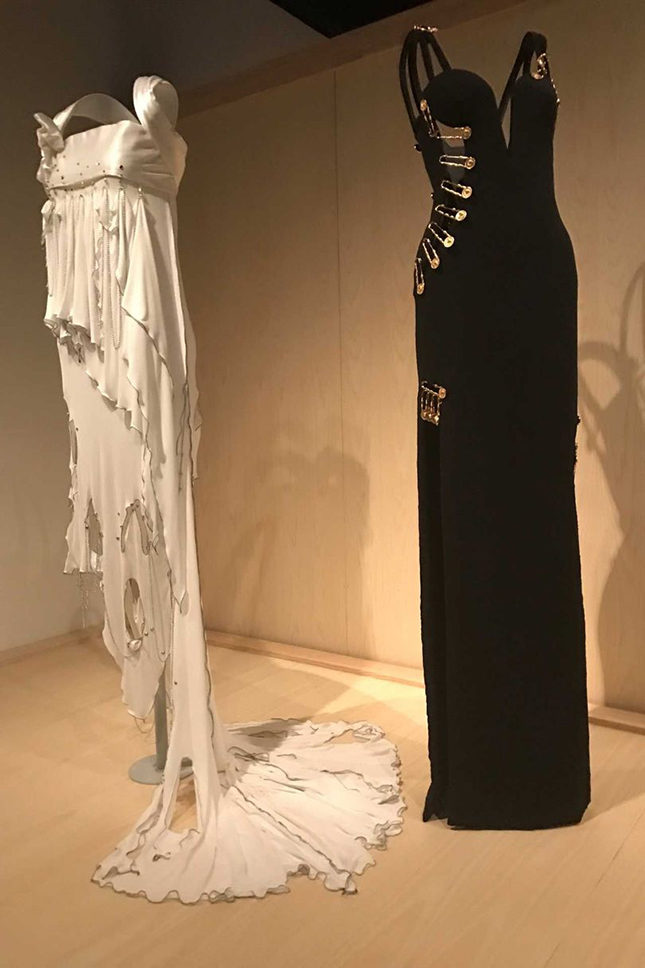 "Left: ""Punk"" Wedding Dress by Zandra Rhodes (British, born 1940), Spring/Summer 1977. Made from white silk-rayon jersey and white nylon-rayon satin, embroidered with nickel ball chain, brass beaded safety pins and clear crystals. Gift of Zandra Rhodes, in honour of Harold Koda, 2016 Right: Dress by Gianni Versace (Italian, 1946-1997) remade in 2016 from an original design by Versace (Italian, founded 1978), Spring/Summer 1994. Made from black silk-synthetic crinkle-crepe, with gold-tone metal safety pins embellished with crystals. Gift of Donatella and Allegra Versace, in honour of Harold Koda, 2016"