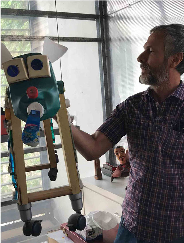 Humberto Campana in his studio with a table of toys made from re-purposed materials