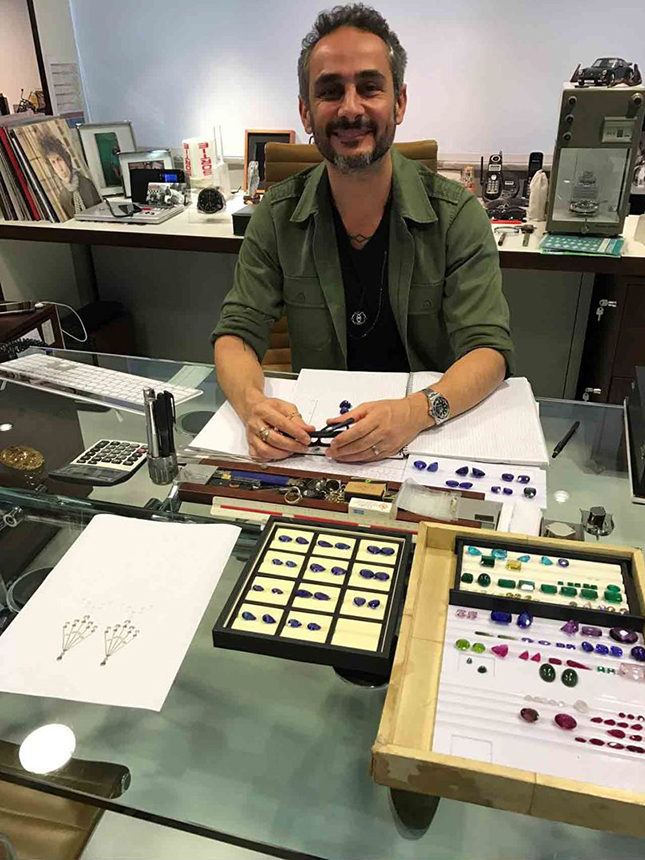 Ara at his desk in his São Paolo studio, surrounded by a collection of stones